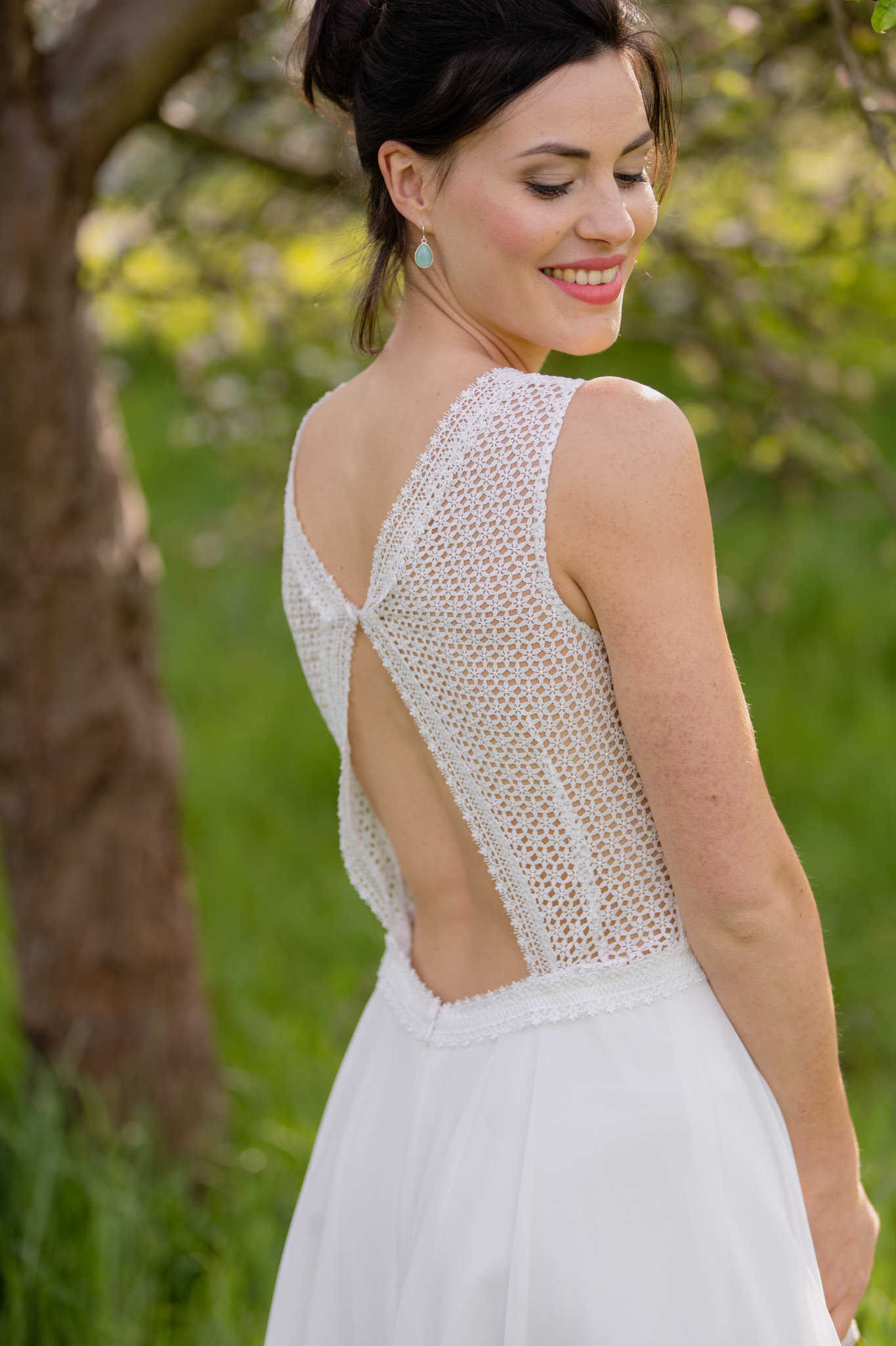 Heather ist ein kurzes Brautkleid, rückenfrei in Szene gesetzt mit Spitze